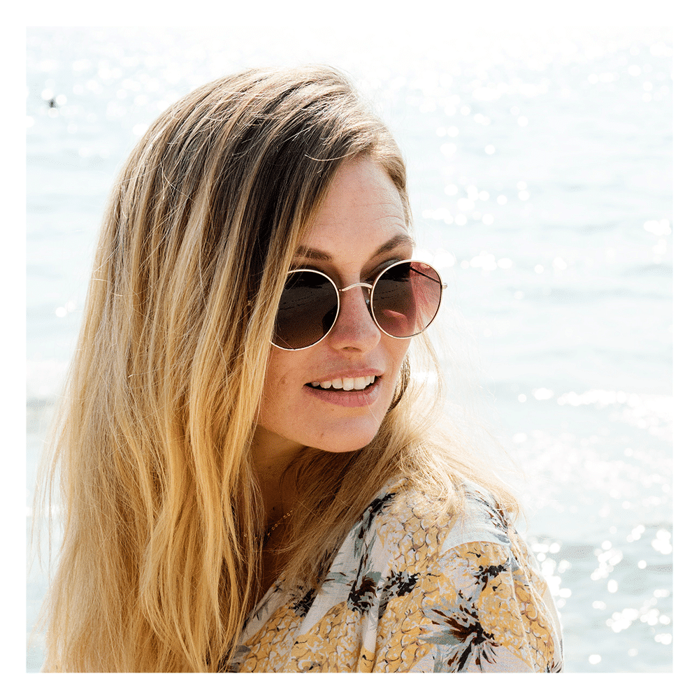 woman by the beach wearing sunglasses