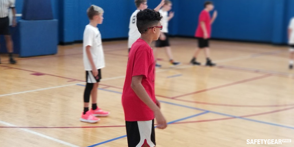 kid in red wearing glasses while playing basketball