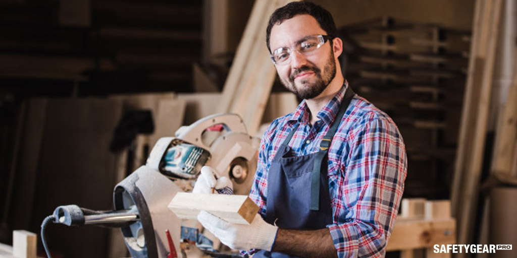 Man doing woodworks while wearing protecting glasses