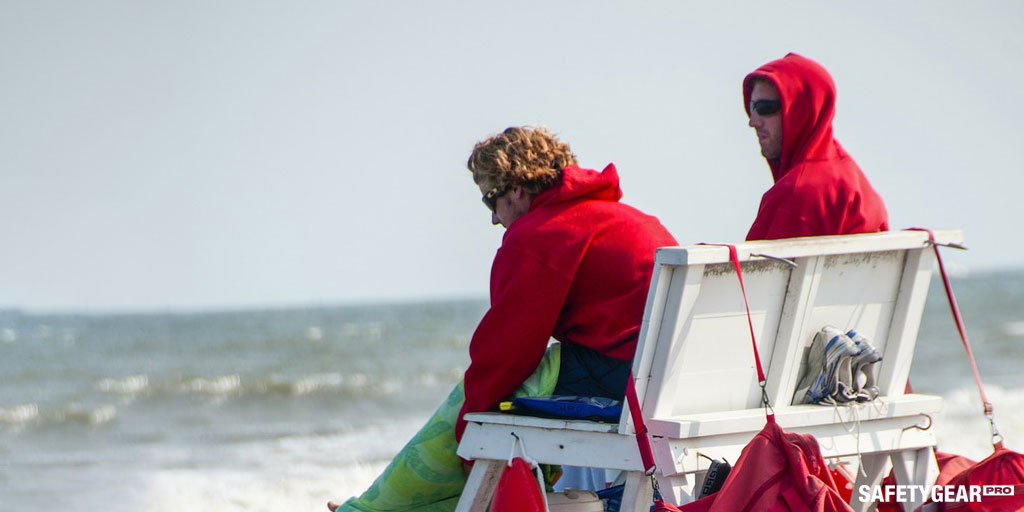 lifeguards on their shift by the beach wearing red