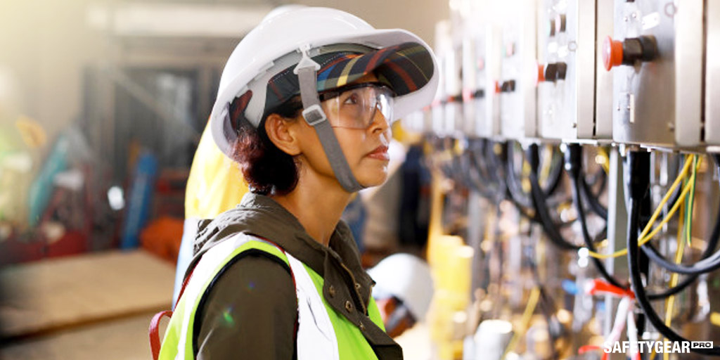 woman wearing hard hat and protective glasses