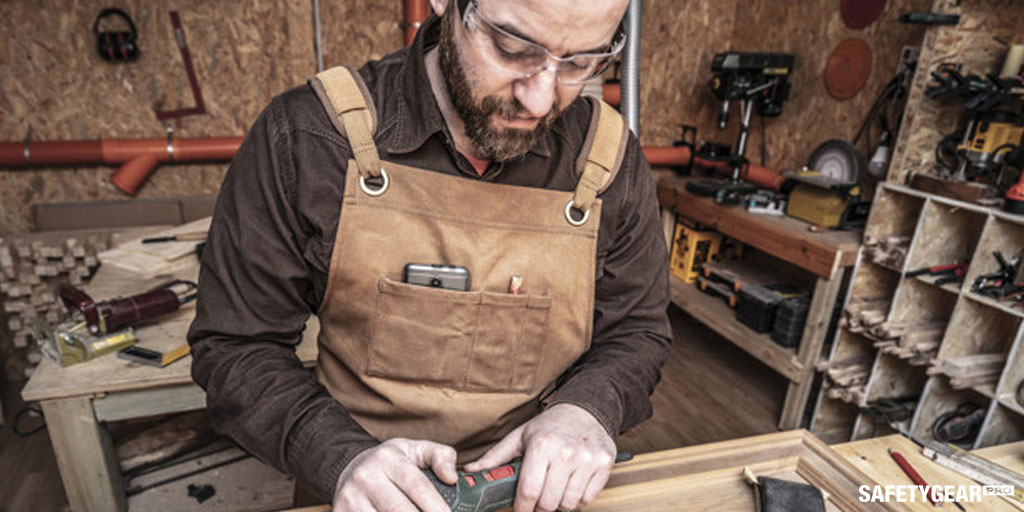 man wearing safety glasses while doing woodwork