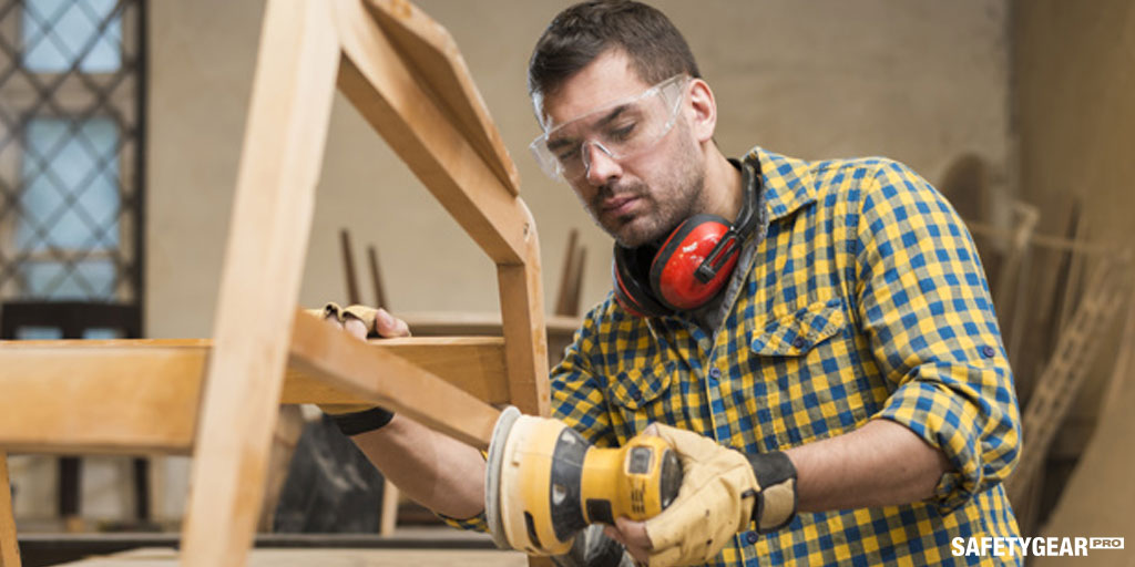 man doing woodwork with safety glasses