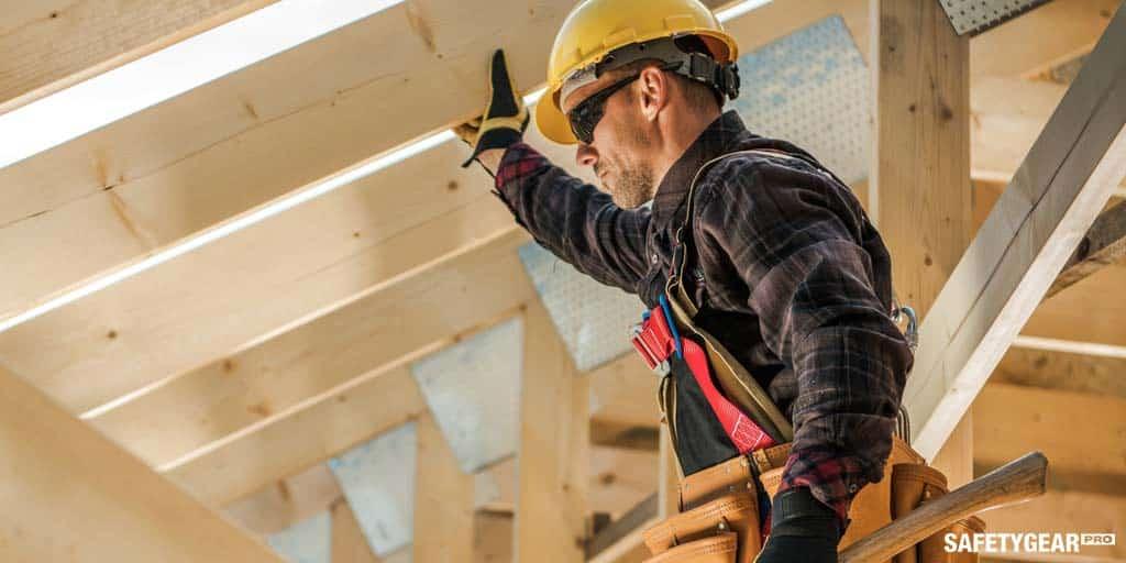 Man wearing hardhat carrying wood
